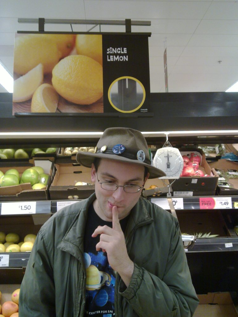 "Paul in a supermarket under a sign that reads ""Single Lemons""."