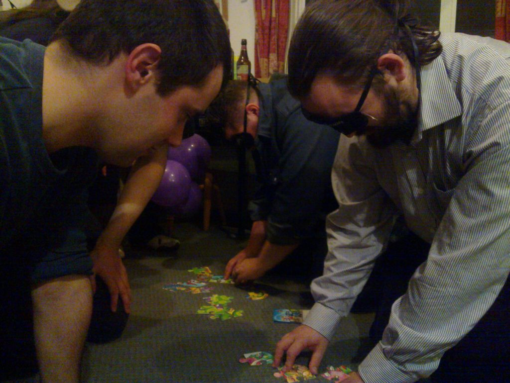 Alec and JTA, blindfolded, attempt to solve jigsaws.