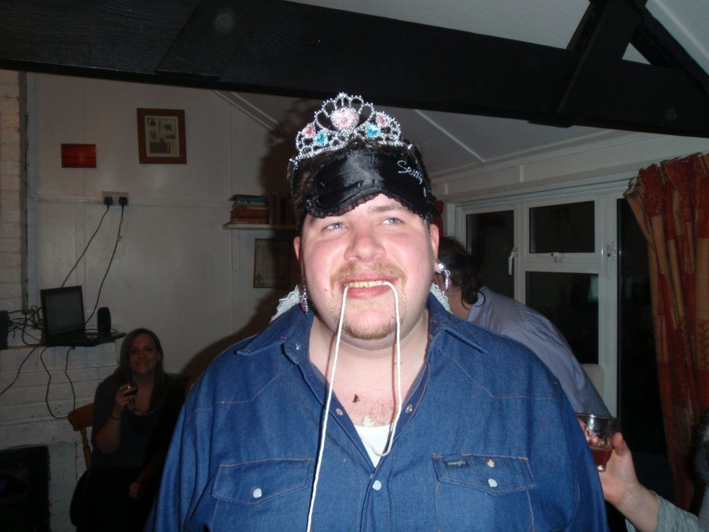 Alec having lost a doughnut-eating competition; still wearing the blindfold, tiara, and earrings from two previous challenges.