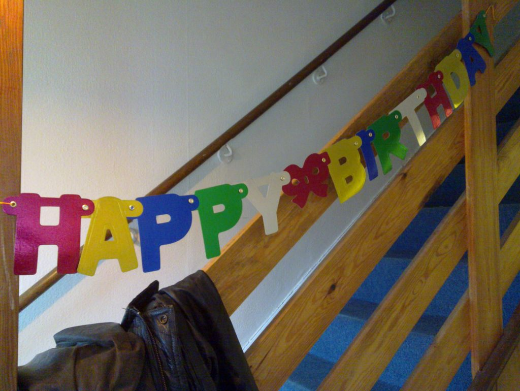 A 'Happy Birthday' banner in the hallway of Earth.