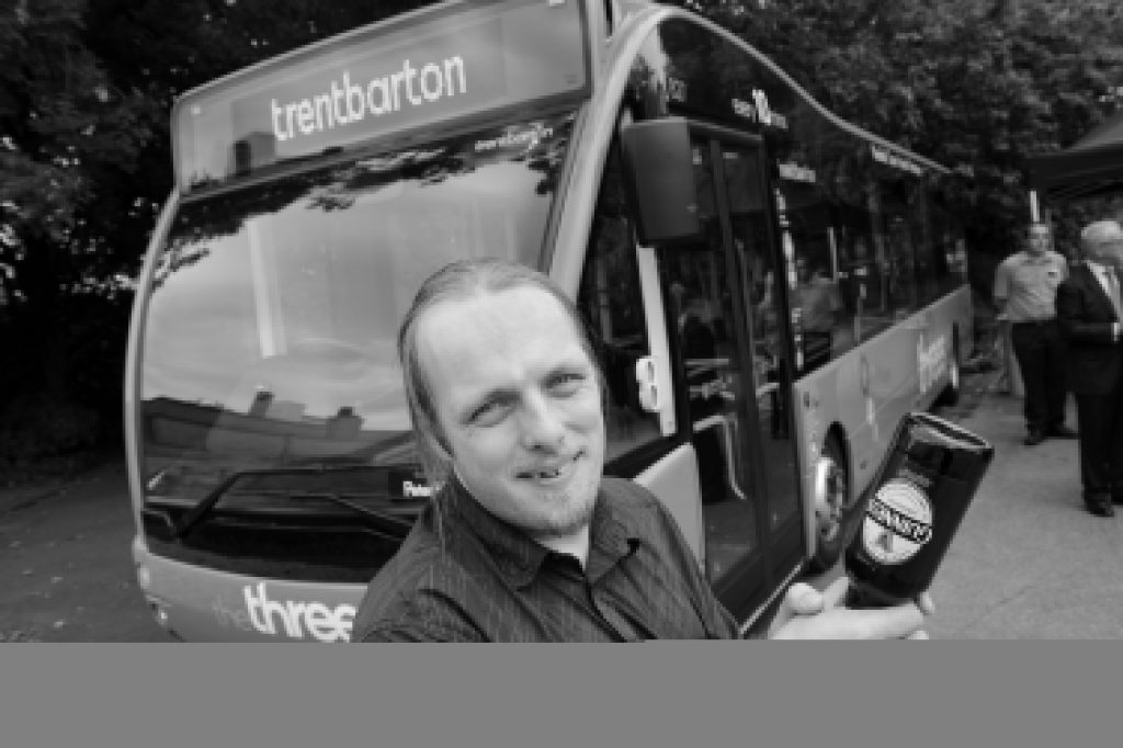 """I hold a bottle of Guinness in preparation of """"breaking"""" it over the front of the bus."""