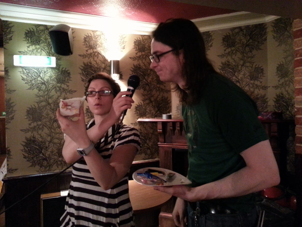Matt R with Helen Arney of Domestic Science, explaining why he's drawn a silicon lattice onto an iced bun.