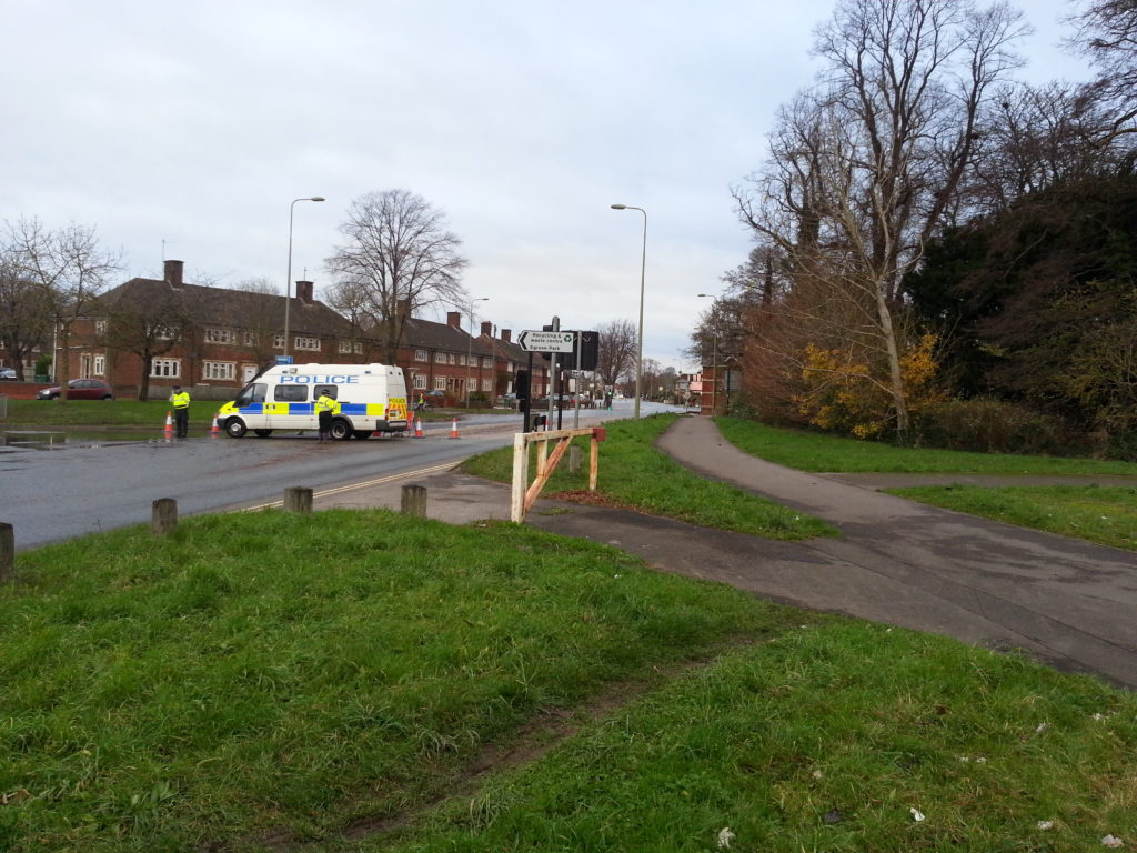 Police direct traffic away from a waterlogged Abingdon Road.