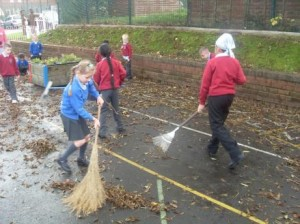 Children sweeping at Holme Slack playground.