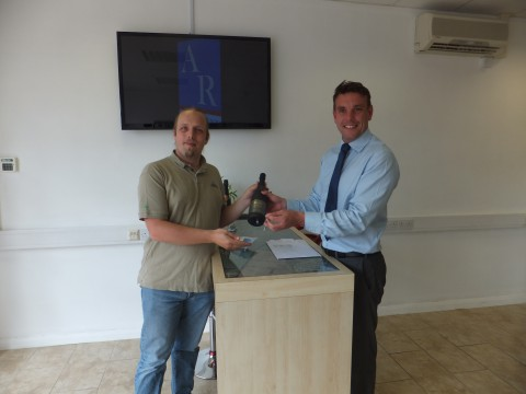 Dan is handed keys and a bottle of sparkling wine by Mark, the estate agent.