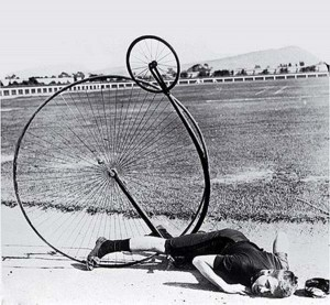 A penny farthing: the rider has tipped over the handlebars and ended up thoroughly upside-down.