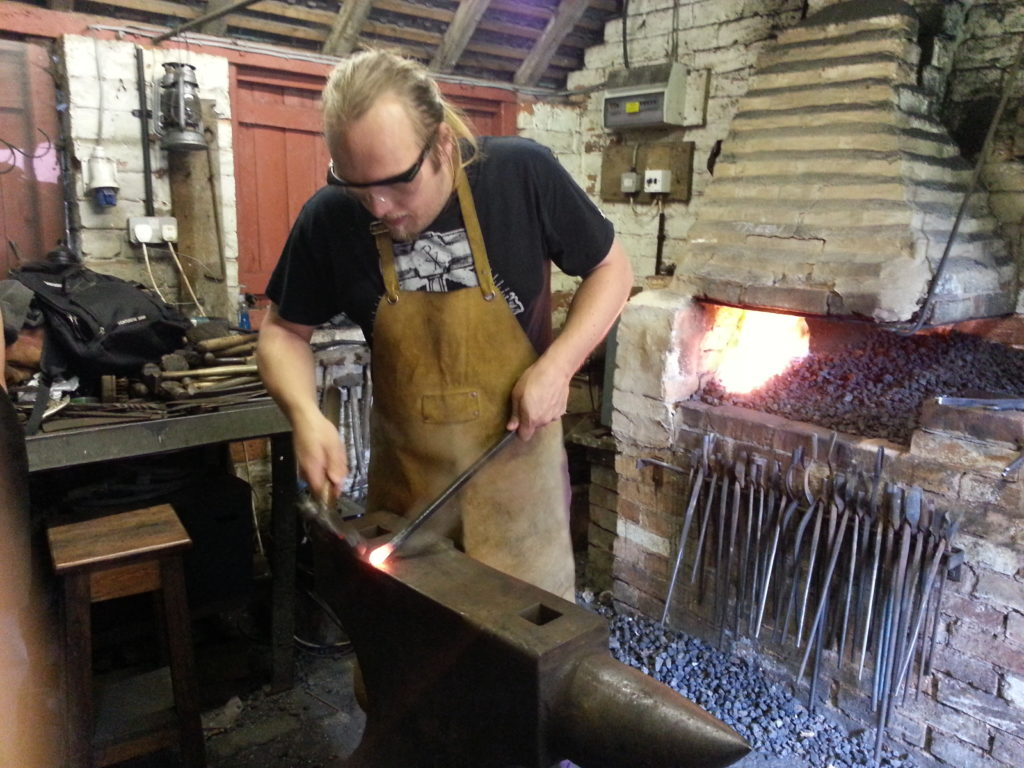 Dan hammers out a point on an anvil.