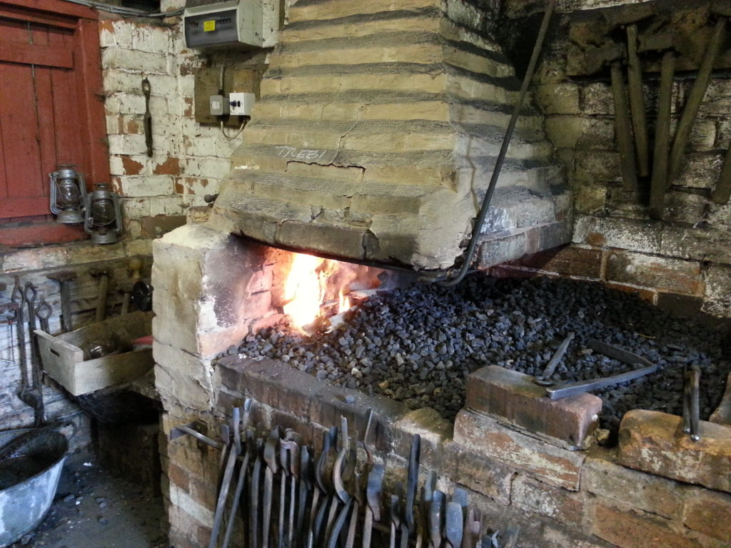 A blacksmith's hearth: the fire is just lit.