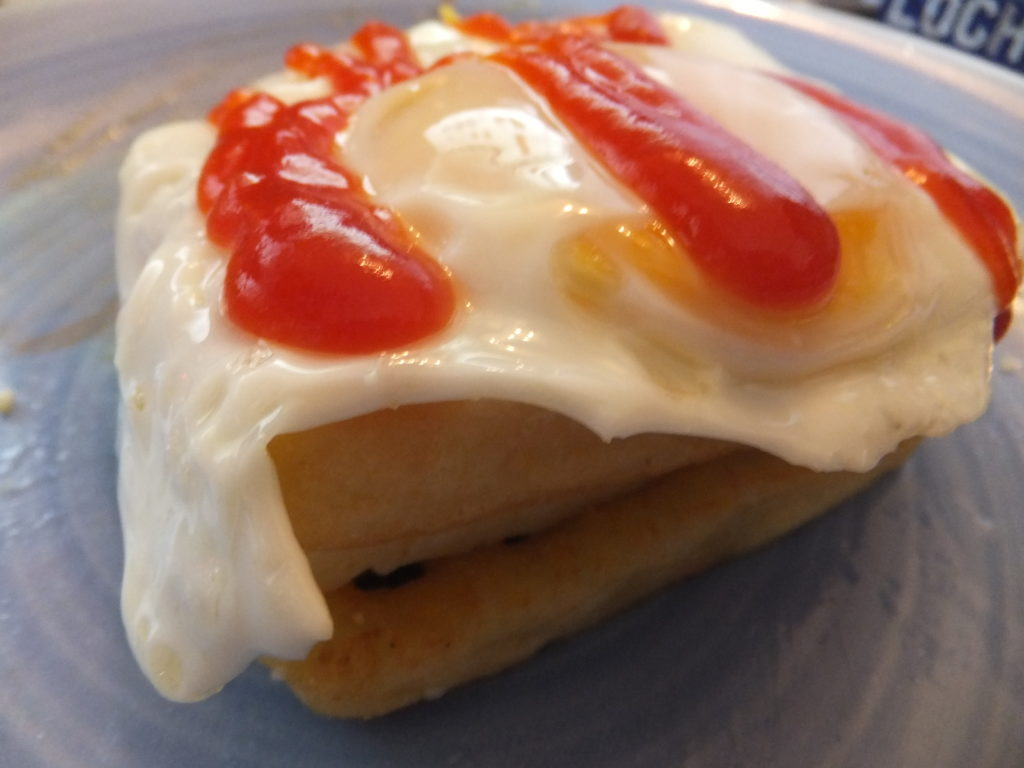 From bottom to top: potato waffle, cheese, potato waffle, egg, tomato ketchup.