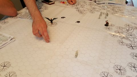 Players fight a basilisk across a paper RPG map.