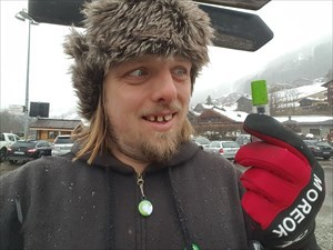 A geocache held by Dan, wearing a snow hat.
