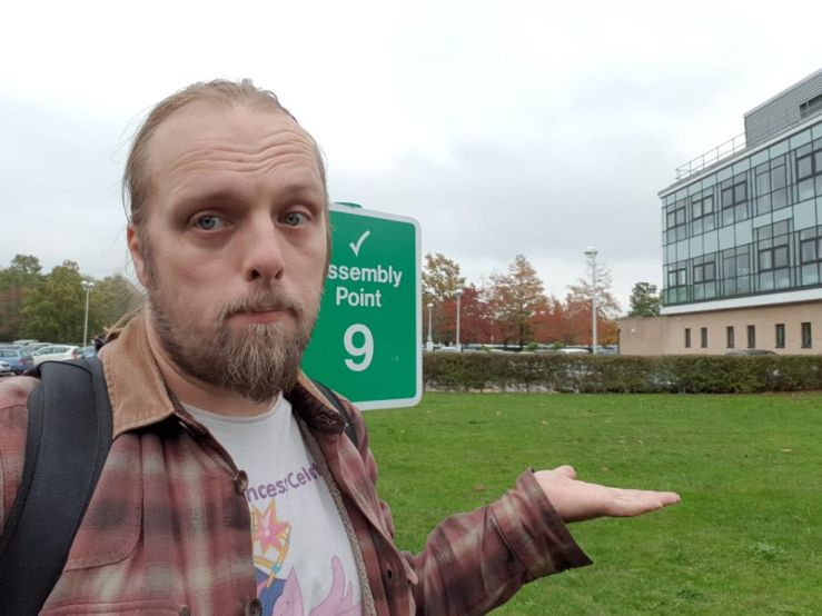 Dan at a Fire Assembly Point sign (at which there possibly once used to be a piece of artwork)