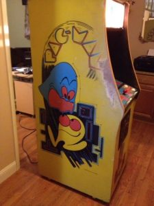 Unrestored Pac-Man machine with worn paint in a specific place on the left-hand side.