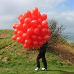 There's a struggle to control the balloons in the wind at the top of the hill