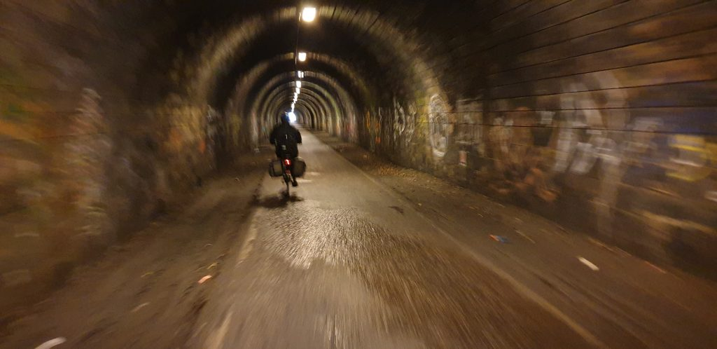 Ruth cycles through the former railway tunnel of The Innocent Railway.