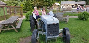 Annabel drives a tractor (with John on the back).