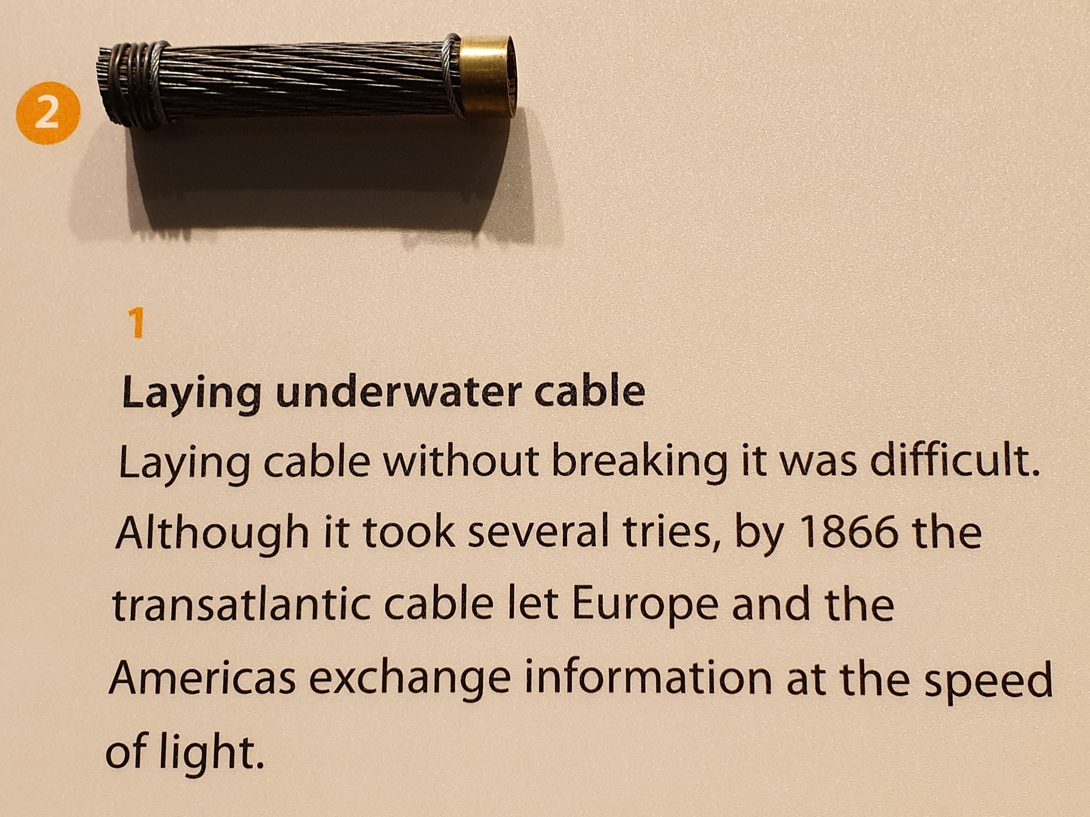 "Exhibit of early transatlantic telegraph cable with message implying that it enabled ""speed of light"" communications."