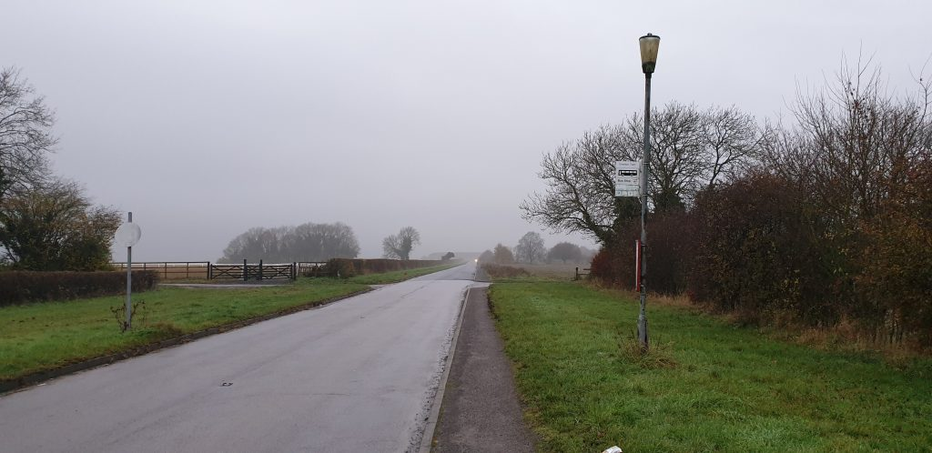Bus stop attached to a lamppost on a misty, empty road.