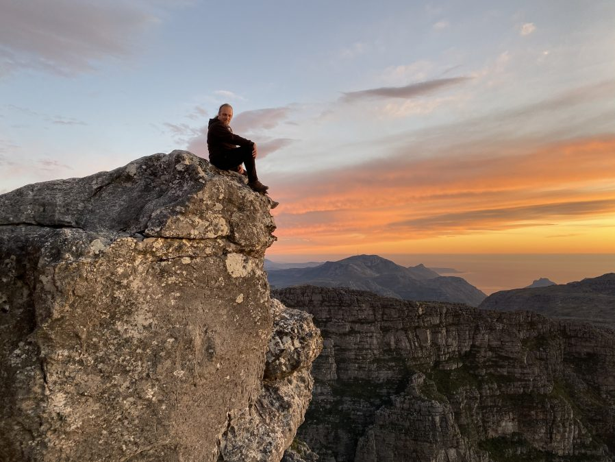 Dan sitting on a rock on Table Mountain, Cape Town, with a sunset in the background