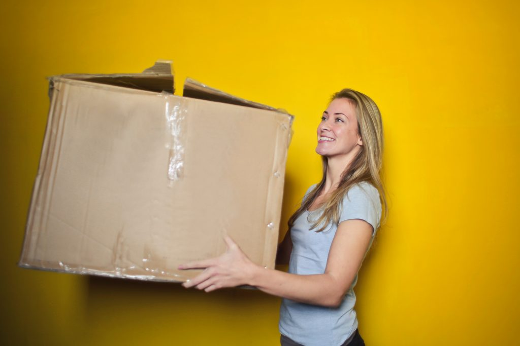 A woman carries a large cardboard box.