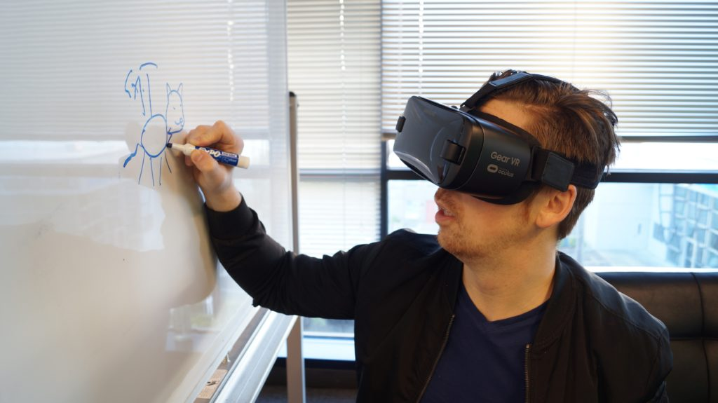A man wearing a VR headset while writing on a whiteboard.