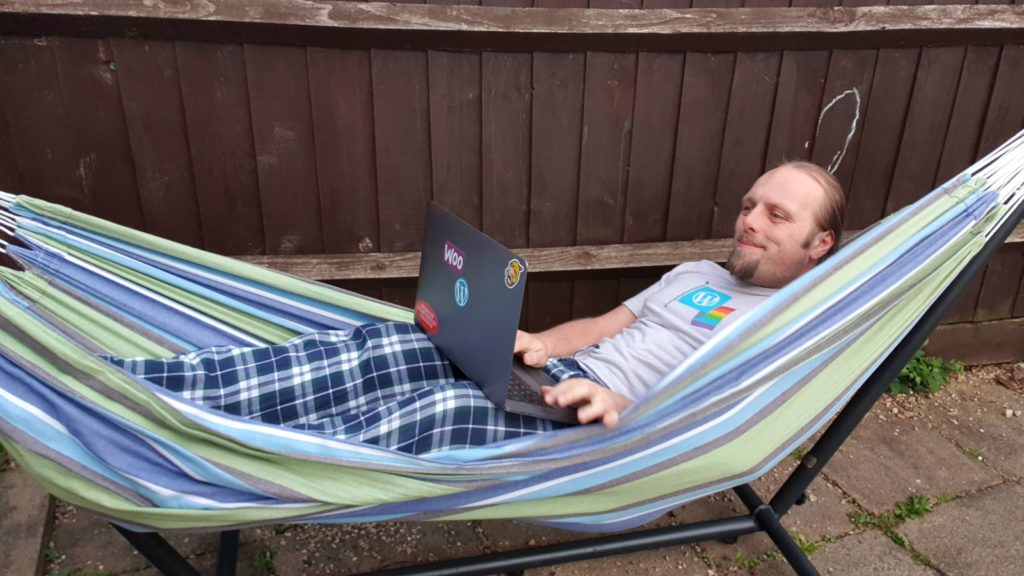 Dan in a video meeting, in a hammock.