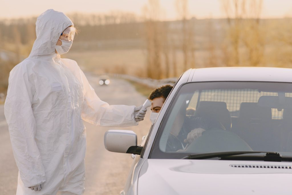 Driver's temperature being checked at the roadside by somebody in full protective equipment.