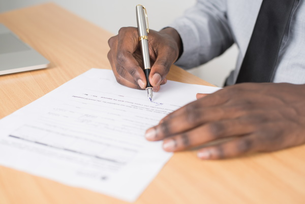 A man signs a document.