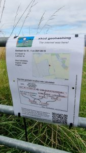 """A """"The Internet Was Here"""" sign explaining geohashing, attached to a gate using zip-ties."""