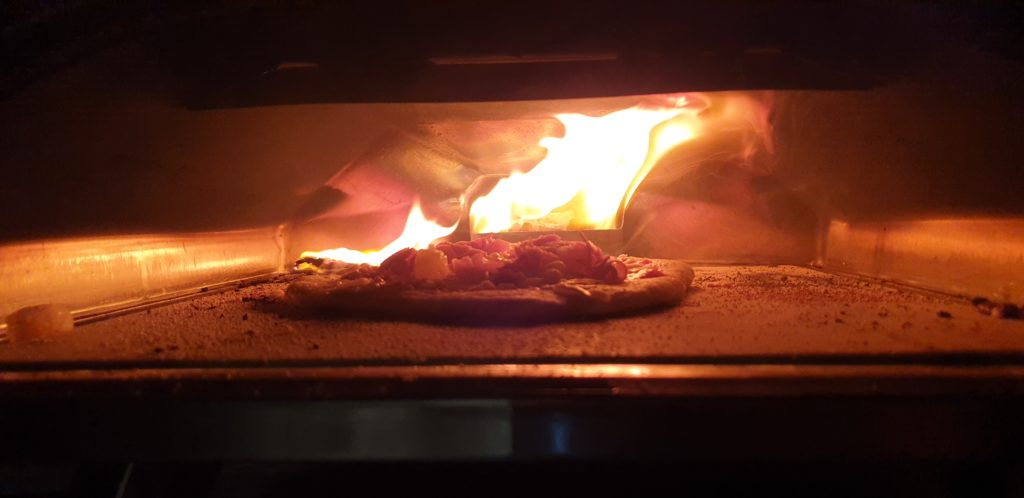 Pizza in an oven, fire raging behind and jumping onto the floor of the oven.