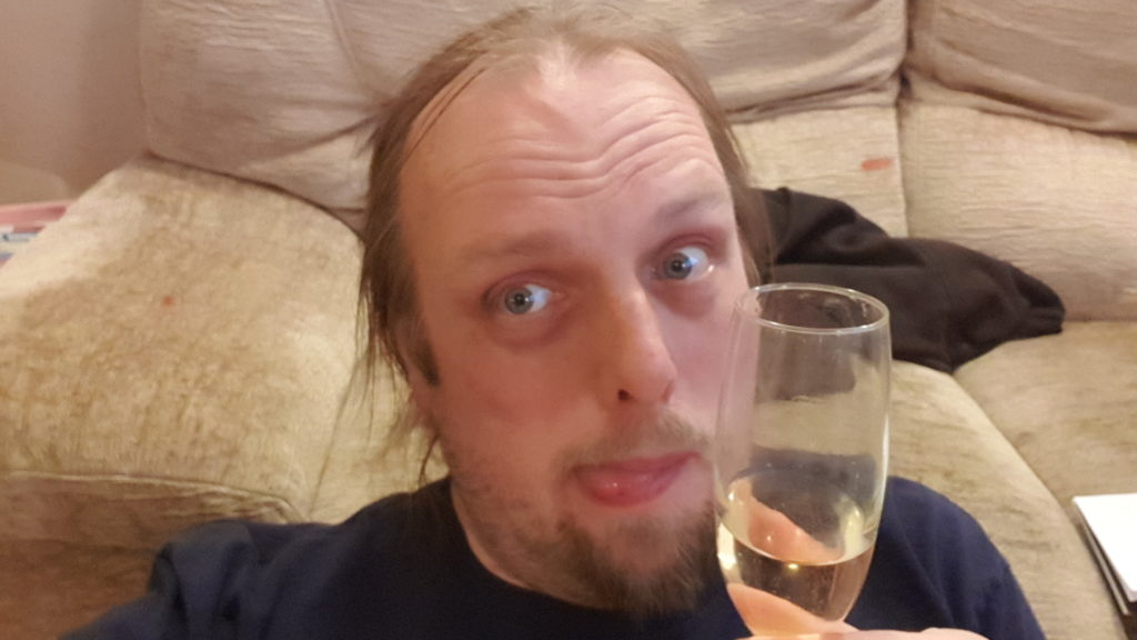 Dan with his tongue out holding a glass of champagne.