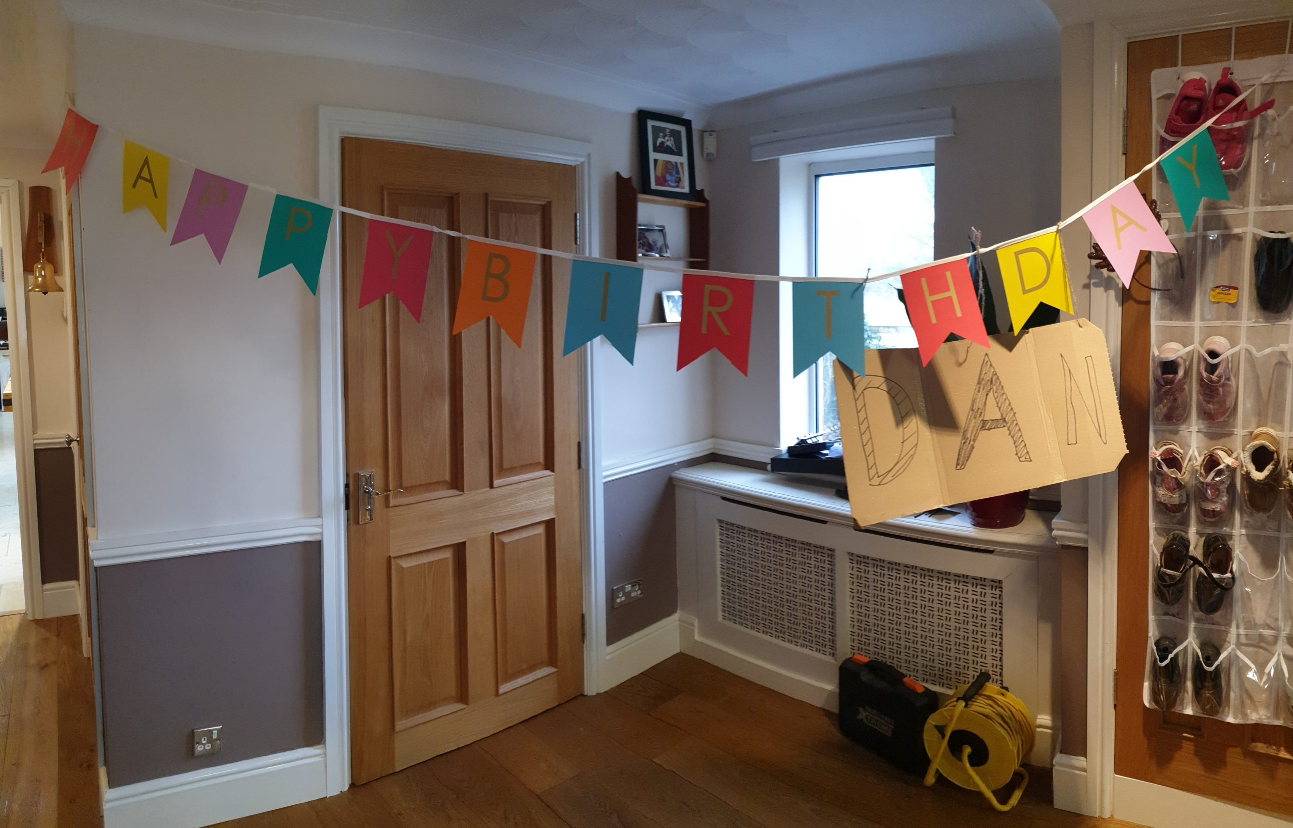"Happy Birthday banner with handwritten cardboard ""Dan"" sign hung underneath."