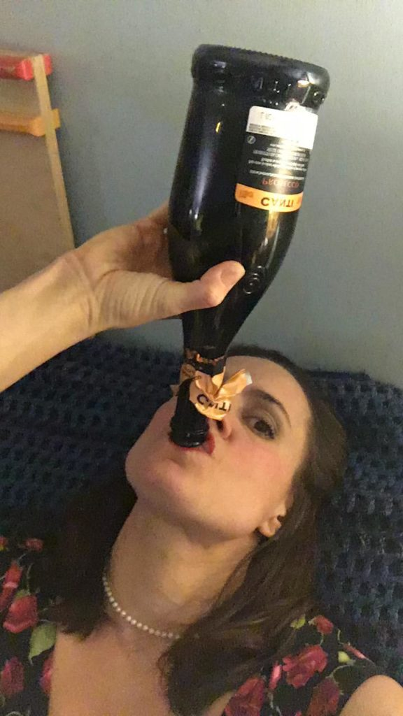 Jen drinking from the neck of a nearly-empty wine bottle.