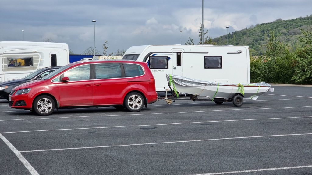 Arthur (red car) and Lucy (rowboat in tow) parked at a service station alongside caravans and HGVs