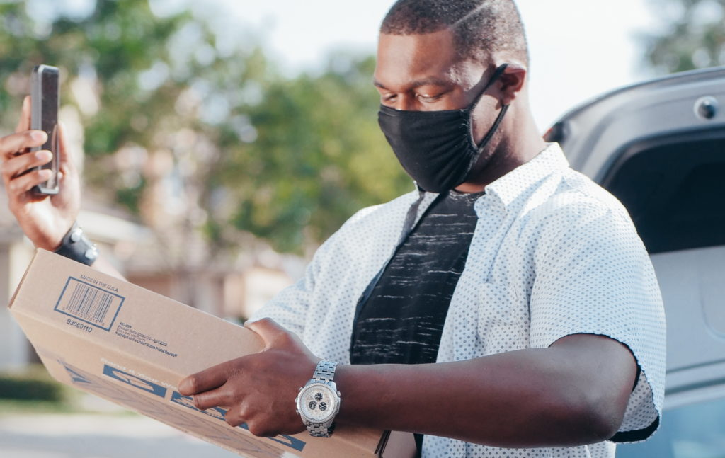 Delivery man, wearing a face mask, holding a parcel and checking his mobile phone. Photo by Kindel Media from Pexels.