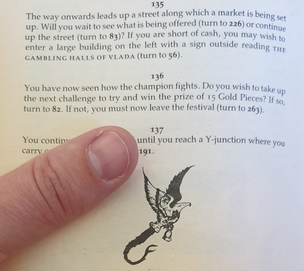 Thumb in the page of a Sorcery choose-your-own-adventure gamebook.