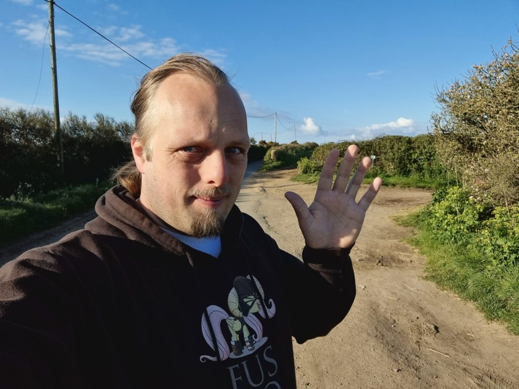 Dan, on a country lane in Cornwall, in front of a bright blue sky, waves to the camera.