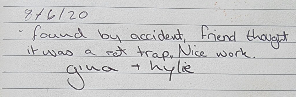 """Handwritten note from the geocache log: """"8/6/20 found by accident, friend thought it was a rat trap. Nice work. gina + kylie"""""""