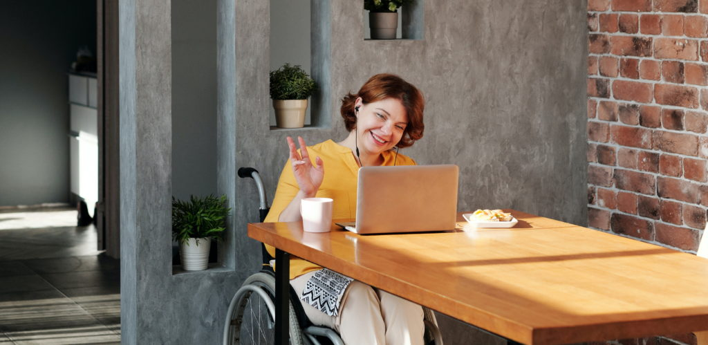A woman in a wheelchair waves to a colleague via her laptop screen; she's smiling and has a cup of coffee by her side. Photo by Marcus Aurelius from Pexels.
