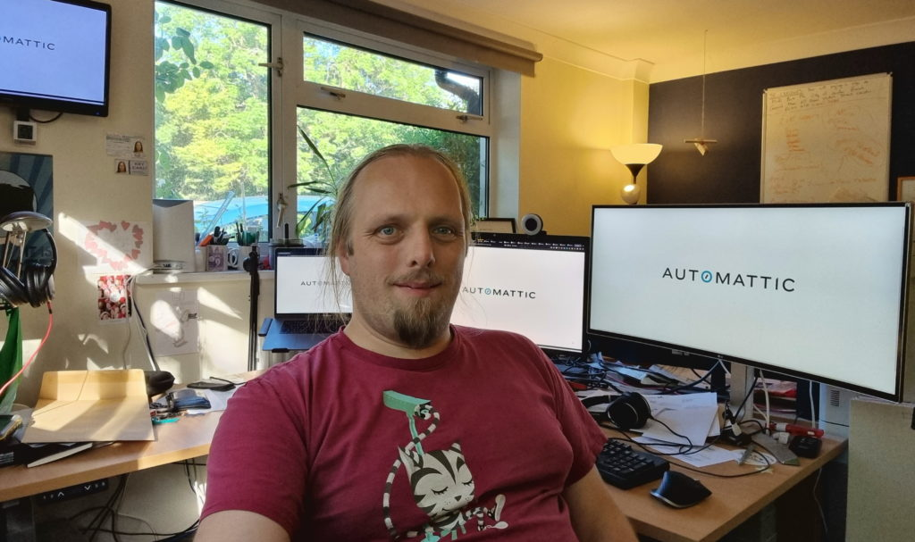 Dan sits in his office; behind him, four separate monitors show the Automattic logo.
