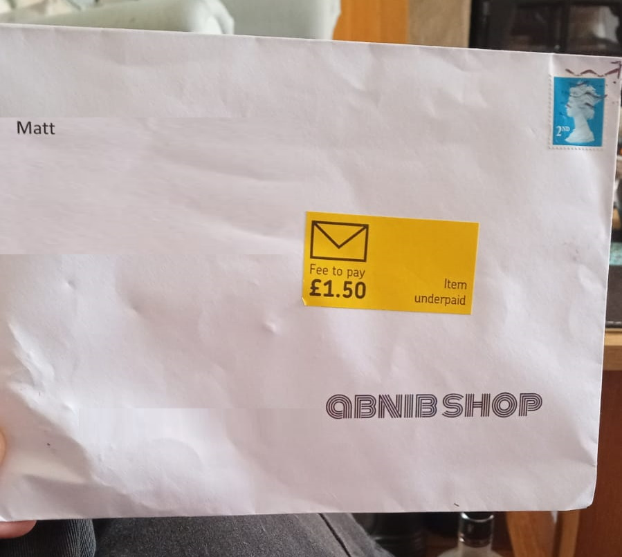 """C5 envelope with a yellow """"Item underpaid. Fee to pay £1.50"""" sticker attached."""