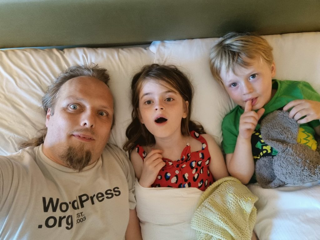 Dan and the kids in a bed at a hotel.