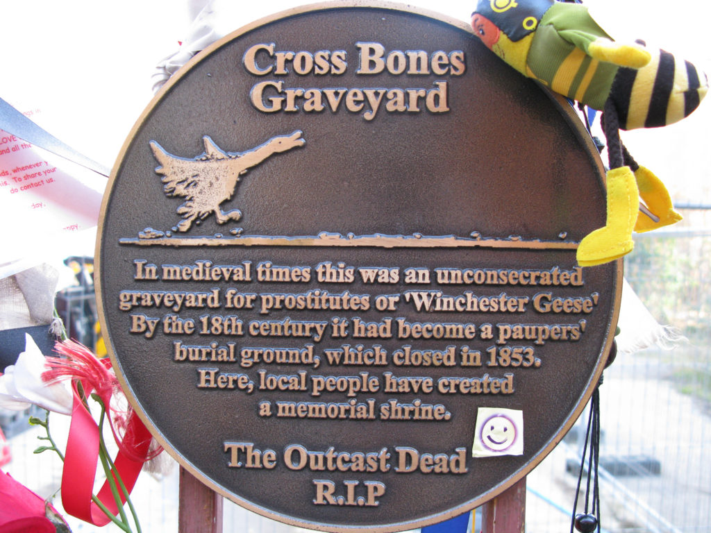 """Plaque with a picture of a goose running and text: """"Cross Bones Graveyard. In medieval times this was an unconsecreated graveyard for prostitutes of 'Winchester Geese'. By the 18th century it had become a paupers burial ground, which closed in 1853. Here, local people have created a memorial shrine. The Outcast Dead R.I.P."""" A smiley face sticker has been attached to the plaque and ribbons and silk flowers are tied nearby."""
