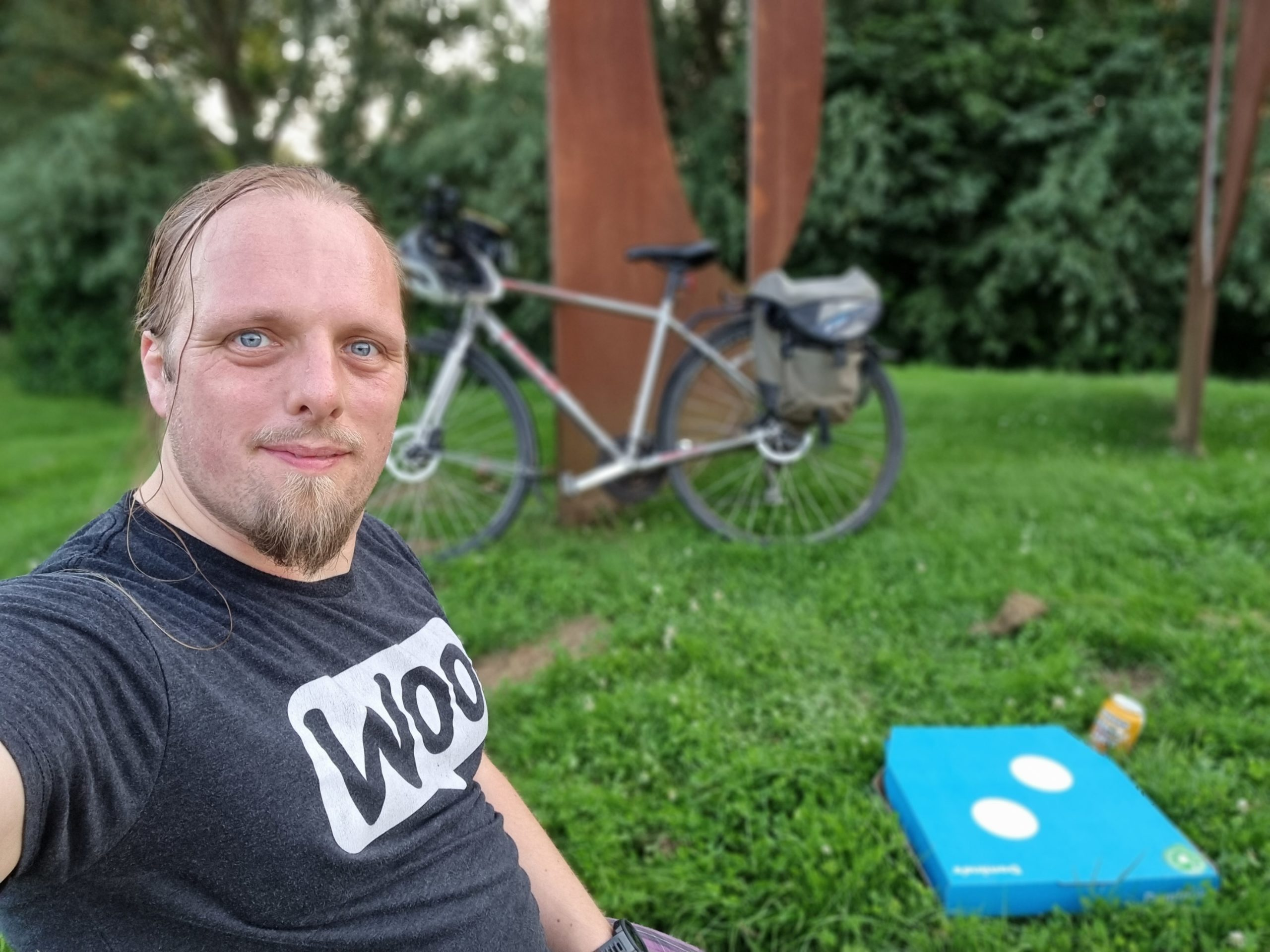 Dan sits on the grass with a Dominos pizza box and a can of beer. His bike is in the background, leaning on a stylistically-corroded piece of metal artwork.