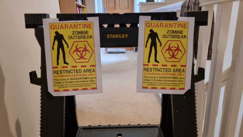 """Barricade with signs reading """"Quarantine: Zombie Outbreak"""""""
