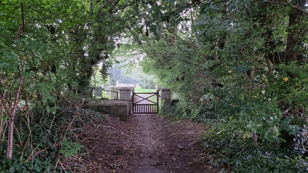 Churchyard gate at the end of a tree-lined path.