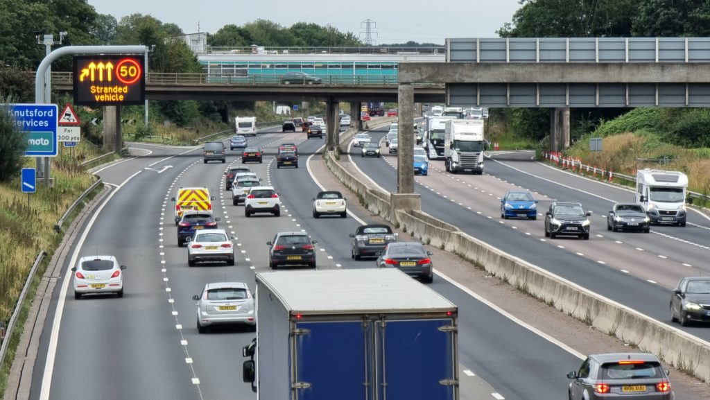 """Motorway traffic moving past a 50 limit and """"stranded vehicle"""" warning sign."""