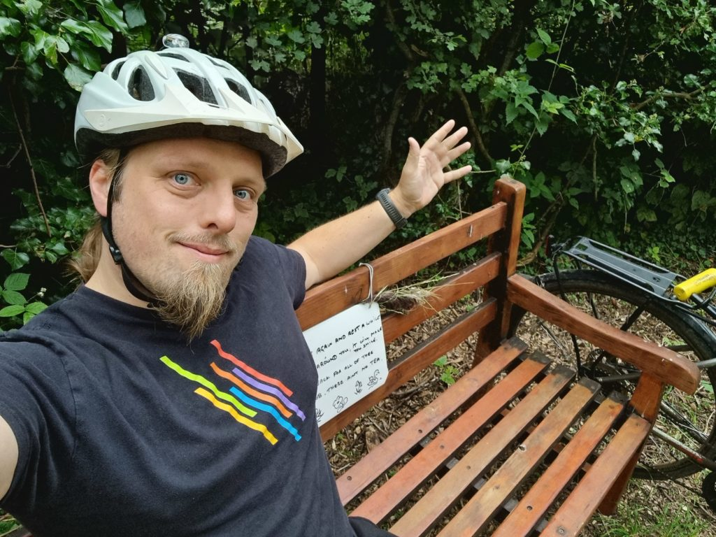 Dan wearing a cycle helmet sitting on a wooden bench.