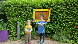 The kids learn from a Mr. Tumble screen.