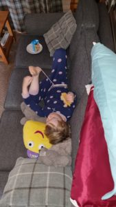 Lounging on the sofa with a CBeebie toy.